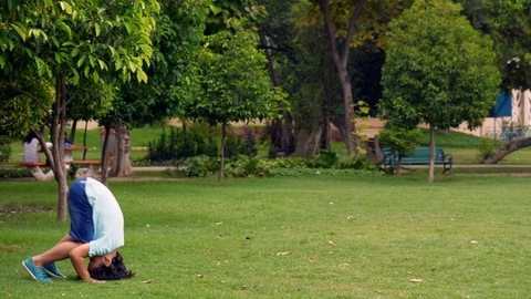 Cute Indian kid continuously doing somersaults in a park - outdoor activities to stay healthy