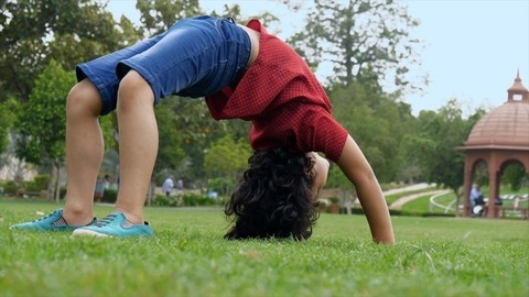 The young flexible child happily doing Chakrasana or wheel pose in a park