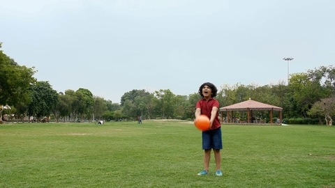 Cute Indian kid in casual clothing playing with a small basketball - childhood fun