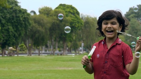Handsome Indian boy cutely blowing soap bubbles and enjoying his evening playtime