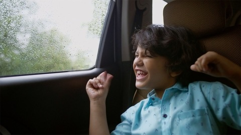Happy Indian child enjoying music while traveling back home in a car - childhood concept
