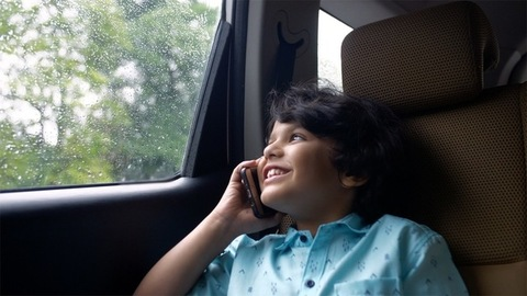 Handsome Indian boy happily talking to his friend over a phone call - technology concept