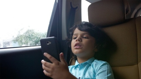 Young innocent kid busy doing a video call from his smartphone - modern technology