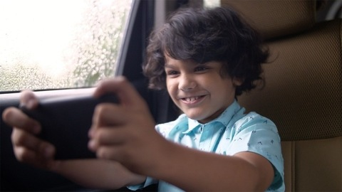 Young handsome kid playing video games on his mobile phone - lifestyle kids