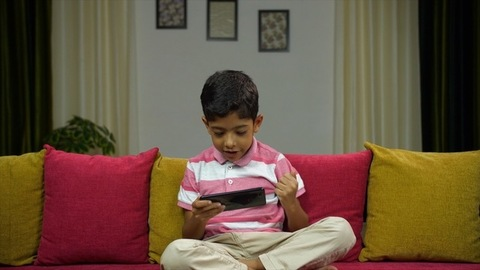 Young cute boy playing game on his smartphone at home - leisure lifestyle