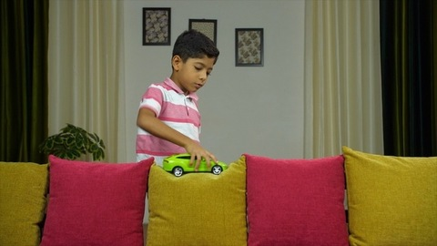 Smiling Indian boy playing with his toy car in the living area - kids lifestyle concept