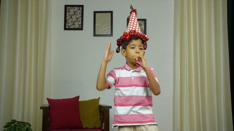 Happy Indian boy having fun with noise maker at a birthday party - lifestyle kids