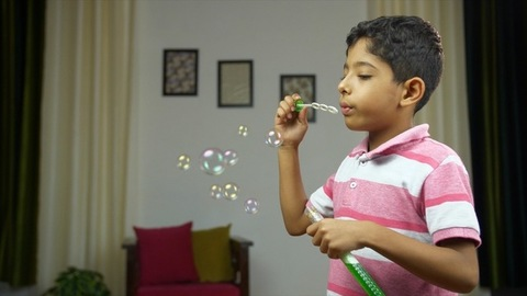 Young Indian kid cutely blowing soap bubbles in his summer vacations - playtime