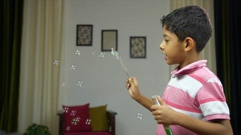 Young cute boy enjoying and making soap bubbles in casual clothing - childhood fun