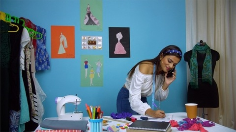 Young fashion designer happily taking customer orders over a phone call - Designer studio