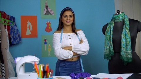 Happy young Indian fashion designer confidently dressing a mannequin in her fashion studio