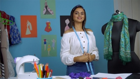 Young dynamic fashion designer smiling while wearing a measuring tape around her neck
