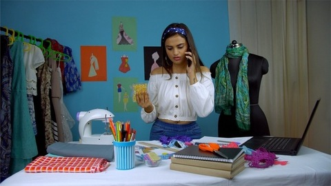 Indian female designer working in her fashion boutique and talking on the phone