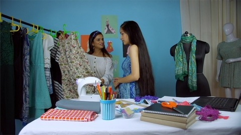 Young female retail entrepreneur showing the new dress collection to her customers