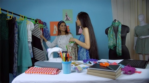 Indian fashion designer dealing with a client in her small fashion atelier - Young businesswoman