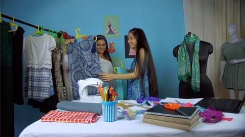 Young female retailer dealing with her customer at her small fashion boutique - Female checking new dresses