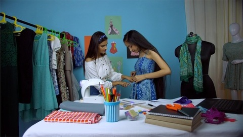 Attractive female entrepreneur happily doing her work at her fashion atelier