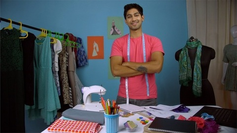 Indian male fashion entrepreneur happily smiling at the camera with folded arms - fashion studio