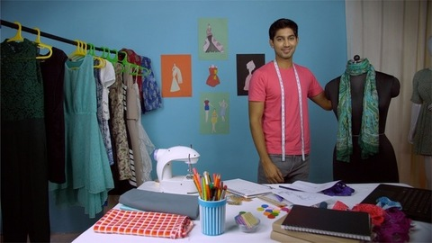 Young male fashion designer styling the mannequin with a scarf at his fashion studio