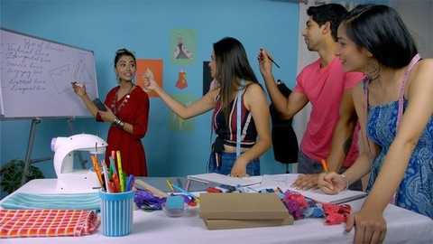 Young female college teacher teaching her students in a fashion studies lab