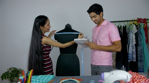 Young successful fashion designers measuring a mannequin in their fashion boutique