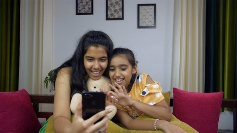 Younger and older sisters busy doing video call with a smartphone - technology concept