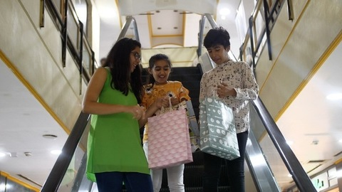 Front view of young Indian siblings happily coming down from moving stairs at a shopping mall