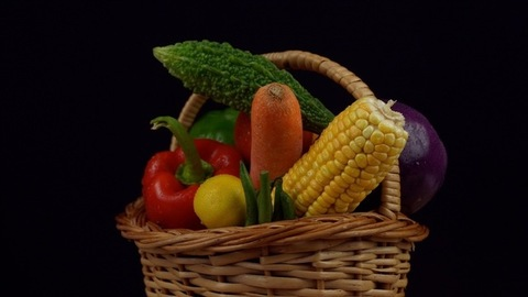 A beautiful basket of fresh vegetables against the black background - healthy lifestyle