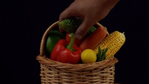 Hand of an Indian man picking up bitter gourd from a vegetable basket - black background