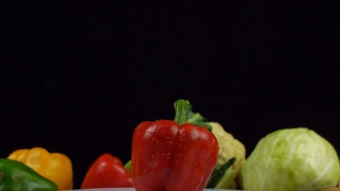 Red bell pepper (capsicum) in a white plate rotating on a turntable - healthy vegetables