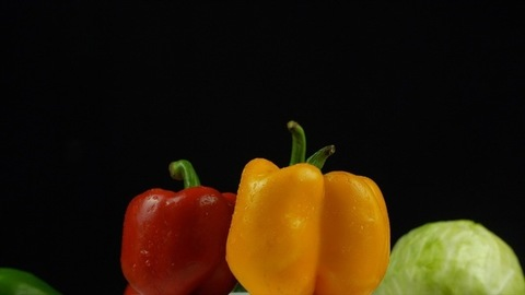 Fresh yellow, red, and green capsicums rotating on a turntable - black background