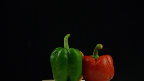 Three different colored bell peppers (capsicums) isolated against the black background