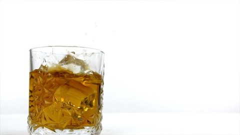 Big ice cubes dropping in a transparent glass of golden whiskey
