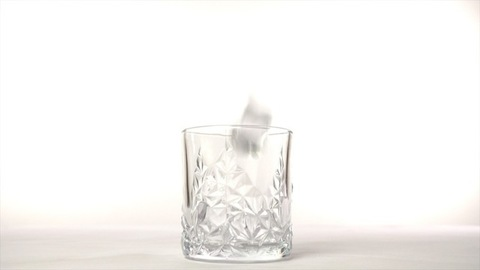 Four big ice cubes dropped in an empty glass of whiskey against a white background