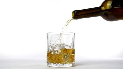 Golden whiskey poured into a crystal clear glass from a brown bottle