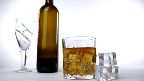 A glass of whiskey placed near ice cubes against a white background