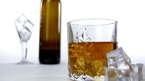 Crystal clear whiskey glass kept on a table with ice cubes placed near it