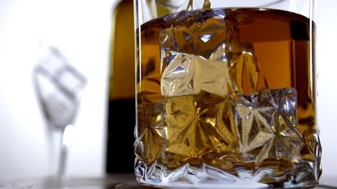 Rotating crystal glass of golden whiskey with big ice cubes filled in it