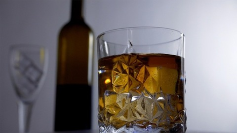 Beautiful view of a rotating glass of whiskey filled with big ice cubes
