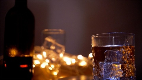 Racking shot of a glass of whiskey filled with ice cubes ready to drink