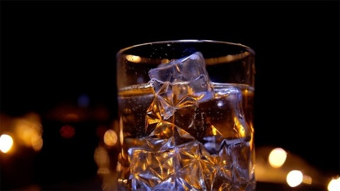 Golden whiskey in a rotating crystal glass with ice cubes dropping in it