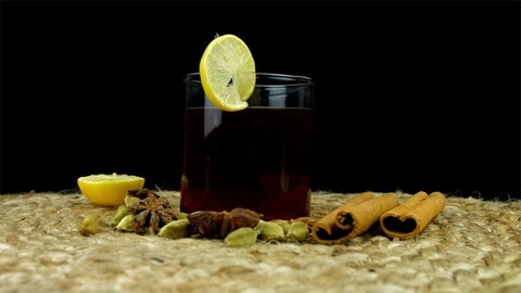 Rotating cup of green tea decorated with a lemon slice kept on a jute mat
