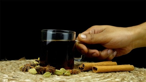 Male's hand picking up and putting down a cup of green tea against black background