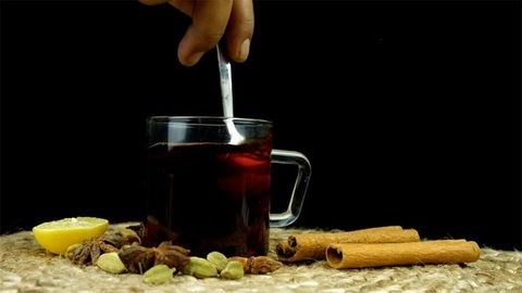 Preparing a cup of green tea with different Indian spices