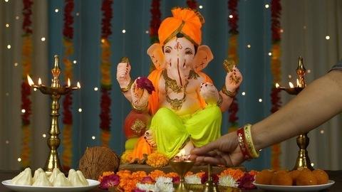 Shot of an Indian female's hand lighting up a diya / lamp for puja of Lord Ganesh Ji