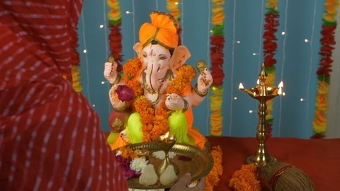 Overhead shot of an Indian female worshipping Lord Ganesha on Ganesh Chaturthi