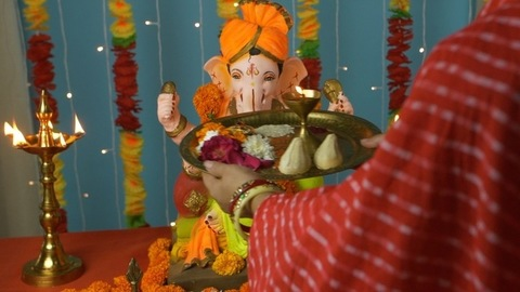 Overhead shot of an Indian female worshipping Lord Ganesha with Puja thali on Ganesh Chaturthi