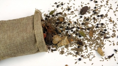 A blend of traditional Indian spices in a small sack of jute isolated over white background