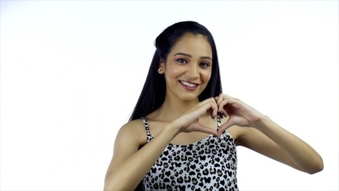 A young attractive girl smiling and showing the heart sign - love concept