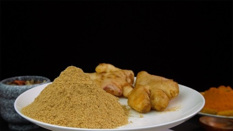 Fresh roots of ginger with dry ginger powder in a rotating white plate - healthy spices of India